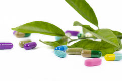Capsules with leaves. Colored capsules with leaves on white background Royalty Free Stock Photo