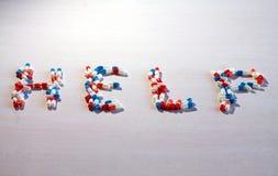Capsules médicinales colorées formant l'aide de mot photo stock
