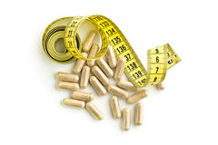 Capsules and measuring tape. Stock Photography