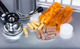 Capsules and medicine bottles plus medical equipment on stainles Stock Photography