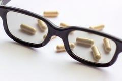 Capsules met glazen op lichte achtergrond Apotheek en geneeskunde voor ogenconcept royalty-vrije stock fotografie