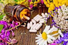 Capsules in open brown jar on board with flowers Stock Images