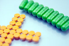 Capsules and pills. Green Capsules and yellow pills  on a blue background Royalty Free Stock Photos