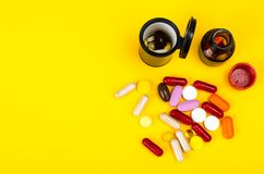 Capsules, pills on yellow background. Concept of health and pharmacology. Studio Photo Stock Photos