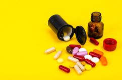 Capsules, pills on yellow background. Concept of health and pharmacology. Studio Photo Royalty Free Stock Images