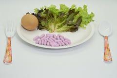 Capsules pourpres avec l'oeuf, la salade, la cuillère et la fourchette sur le blanc d'isolement photo libre de droits