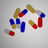 Capsules. Red and blue and yellow capsules on white background Stock Photography