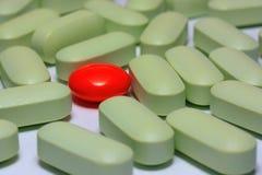 Capsules rouges des comprimés de différentes couleurs Photos stock