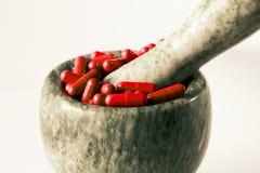 Capsules rouges et pilules oranges avec des pilons de mortier sur le fond blanc Photo stock