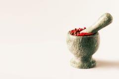 Capsules rouges et pilules oranges avec des pilons de mortier sur le fond blanc Photographie stock libre de droits