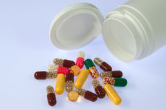 Capsules spilling out from bottle Stock Images
