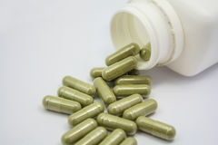 Capsules spilling out of a bottle. Herbal capsules spilling out of a bottle Stock Images