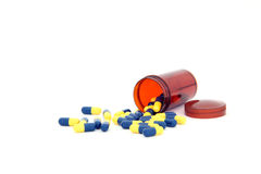 Capsules spilling out from small bottle Stock Photography