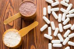 Capsules van creatine en eiwit metende lepels Stock Foto