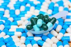 Capsules vertes dans la cuillère de pilule sur beaucoup de capsules bleues blanches Image libre de droits
