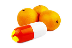 Capsules with vitamins and three oranges. Stock Images