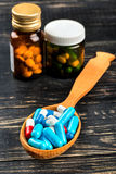Capsules in a wooden spoon Stock Photos