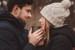 A captação do estilo de vida dos pares felizes que bebem o chá quente exterior em acolhedor aquece a caminhada na floresta imagem de stock