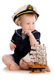 Captain. Portrait of the cute child in a sea clothes with the model ship Royalty Free Stock Photos