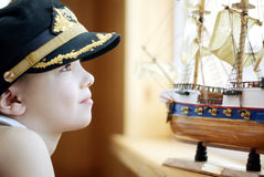 Captain. Portrait of the young boy with the model ship Royalty Free Stock Photo