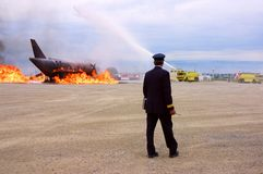 Captain. A fire chief coordinating with a walkie-talkie the actions of two yellow fire trucs attending to a burning plane Stock Photos