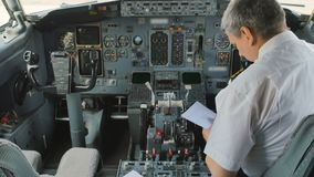Captain of airplane prepares to flight and fills documents. Captain of airplane prepares to flight and checks some documents. The man is sitting in cockpit and stock video