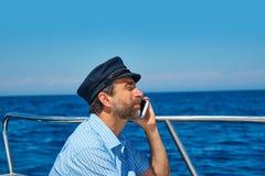 Captain al hombre del marinero del casquillo que habla el barco del teléfono móvil Imagenes de archivo