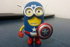 Captain America Minion. Toy dressed with his blue and red suit, holding red, silver, blue shield with the star logo stock photos