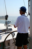 Captain beyond the yacht steering. Directing into the sea Royalty Free Stock Photo