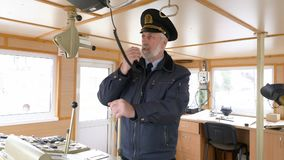 Captain in the boat is setting radio communication and said on the transmitter. Elderly grey-haired captain in uniform on the boat in control room is setting stock footage