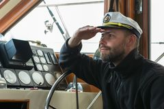 Captain at the helm of boat going along the Pacific Ocean Stock Images