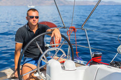Captain at the helm controls of a sailing boat during sea yacht race. Sport. Stock Photography