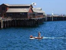 Captain and his ship. The Captain pilots his ship beneath the pier at Santa Barbara Royalty Free Stock Image