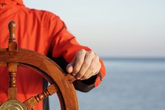 Captain holding hand on ship rudder. Royalty Free Stock Photo