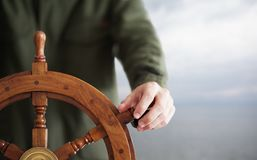 Captain holding hand on ship rudder. Stock Image
