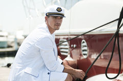 Captain holding rope of the yacht. Young captain looking away and holding rope of the yacht Royalty Free Stock Image