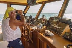 Captain im Beitrag eines Schiffs, das mit Ferngläsern auf der Anzeige aufpasst lizenzfreies stockfoto