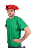 Captain India. A young Indian guy wearing a red ship captain hat, on white studio background Royalty Free Stock Photography