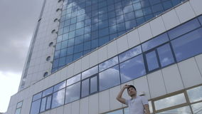 A captain near a tall hotel with a reflection of the clouds stock video