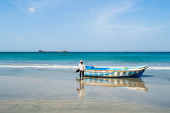Captain at Nilaveli Beach in Sri Lanka with Pigeon Island in the Back royalty free stock photo