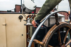 Captain operate an ancient ship steering wheel. Stock Photos
