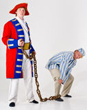 Captain and prisoner. A man dressed in a captain's uniform holding on to a chain, with a prisoner's leg tied to the other end of the chain Stock Images