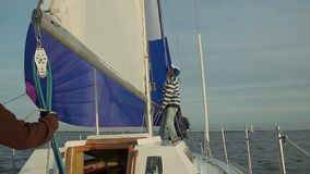 Captain putting up mainsail on beautiful yacht, traveling. Stock footage stock video