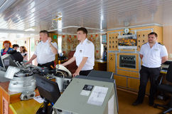 Captain of river cruise ship Alexander Benois and captain`s assistants in captain`s cabin Royalty Free Stock Photo