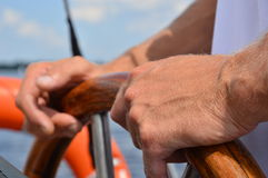 Captain's Hands. Hands holding a wooden steering wheel on a sailboat Royalty Free Stock Image