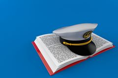 Captain`s hat on open book. Isolated on blue background. 3d illustration Royalty Free Stock Photo
