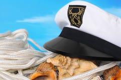 Captain's peak-cap and cockleshells Stock Photos