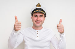 Captain with sailor cap showing two thumbs up. Happy captain with sailor cap showing two thumbs up - isolated on white Stock Photo
