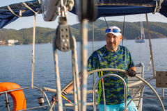 Captain steers the sail boat. Royalty Free Stock Images