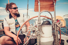 Captain on a yacht behind steering wheel Stock Photo